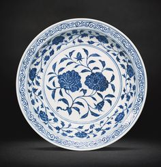 A BLUE AND WHITE 'PEONY' DISH MING DYNASTY, YONGLE PERIOD heavily potted, with rounded sides rising from a tapering foot to a wide everted rim with a rolled lip, the interior boldly painted with a leafy spray bearing two large peony blooms, encircled by an undulating peony scroll, the rim bordered by a foliate scroll, similarly decorated to the exterior with a lotus scroll, the base unglazed revealing the buff-coloured body, Japanese wood box