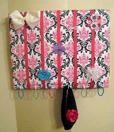 What You'll Need To Make This Canvas Hair Bow Holder: Stretched Canvas (used 11 in x 14 in board- found it in the Art section of Michael's) Fabric (make sure it's ironed!) Quilt Batting (optional) Scissors Staple Gun Cup Hooks (found in hardware stores – I got mine in Walmart) Grosgrain Ribbon Scissors Fabric Glue (optional)