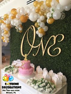 First Birthday party decorations. Irregular balloon arch. Classy and sophisticated. Hedge backdrop and gold ONE sign. Beautifull decorations for this little princess. Party decorations Miami. Balloon decorations.balloon arches. Wedding decorations.