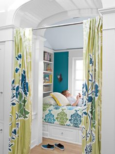 Enclose a cozy nook with colorful curtains to give guests an extra bit of  privacy. Great for the basement to create rooms from open areas