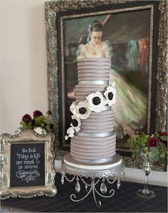 Striking gray contemporary wedding cake.  Nicely set up with the message and simple flowers on the table with the painting in the background.