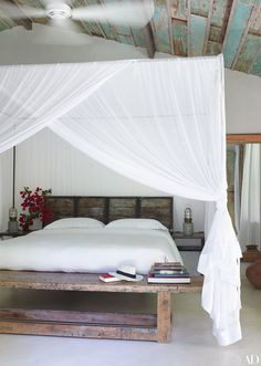 Diaphanous mosquito netting swaddles the bed in one of the guest bungalows.