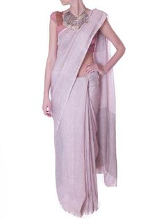 Anavila Misra's linen sarees are made from 100% natural linen woven on a hand-loom. Impeccably chic, this stunning muted pastel pink saree is a stylish option for any event. Stay cool and understated. Style yours with silver choker or silver cuff.  100% linen Comes with blouse piece. Dry clean or hand wash in cold water Designer color: Pink