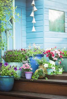 Garden shed painted blue with brown wooden decking and pots full of flowers! Love the windchime too. Easy ways to totally transform your shed!