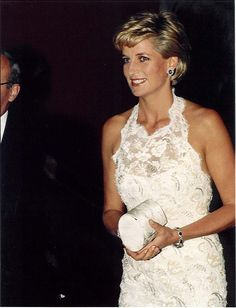 For a fashion sale for breast cancer research in Washington DC in September 1996, Diana wore a long diamante and ice lace sheath evening dress with cutaway, haltered shoulderline by the designer Catherine Walker.