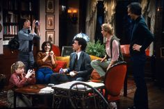 The Set Design of Family Ties: the Keaton's iconic living room, featuring a victorian camelback sofa, Tiffany-style lamp and elaborate swag curtains. Architectural Digest