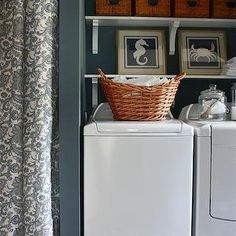 Sarah Macklem Interiors - laundry/mud rooms - Sherwin Williams - Storm - blue gray walls, laundry room paint, laundry room paint colors, blue gray paint, blue gray paint colors, bluish gray paint, bluish gray paint colors, laundry room paint, laundry room paint colors, stacked shelves, laundry room shelves, laundry room baskets, laundry oom storage, beachy art, beach art, blue seahorse art, blue seahorse print, blue crab art, side by side washer and dryer, chevron rug, laundry room rug, blue…