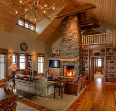 The main living space is wide open yet cozy. The knotty pine ceiling, log railings, fieldstone chimney, antler chandelier and collar ties add rustic style.