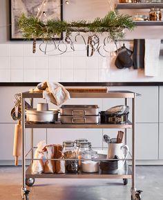 Un supporto per rampicanti appeso sopra a un carrello per cucina, decorato con ramoscelli di stagione e stampi tagliabiscotti - IKEA