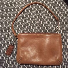 Authentic leather Coach wristlet Chestnut colored wristlet. Minor stain on the back of the bag. No water damage. Good condition. Coach Bags