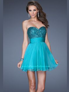Create a dream-like cocktail look in this strapless short prom dress by La Femme 19453. The glamorous sequins that shimmer throughout the sweetheart neckline bodice are placed in a criss-cross way, while the natural waist is well-shaped by a sleek band. A gathered a-line skirt flows to the mid-thigh length. Available in Peacock, Platinum and Purple Mist. Glam it up with jeweled heels and chandelier earrings.
