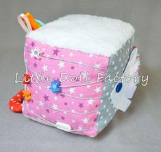 Sensory cube, made of fabric and felt and developing elements on velcro, buttons, ribbons, different kinds of clasps: buttons, knobs. All materials used in this crafts are non-toxic and odour-free. This is a good sensory toy for the baby helping to develop the fine motor and