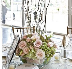 Curly willow branches sprung from low arrangements of pink roses and green hydrangeas.