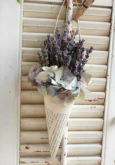 "Vintage French Book Cone with Dried French Lavender and Hydrangea The faded pages of a vintage French book provide the base for this dried arrangement. Freshly dried French Provencal lavender is accented with dried hydrangea. This fragrant bouquet would be a lovely accent for almost any room in your home! Measures approx 8"" from the bottom of the cone to the top of the flowers. The width at the top of the cone including the flowers is approx. 3"". The hanger adds 3"" Please ..."