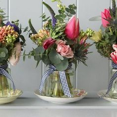 Flowers displayed in jam jars and placed on tea cup saucers.