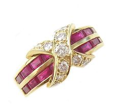 A ruby, diamond and eighteen karat gold ring, Tiffany & Co. designed with two channel-set rows of baguette-cut rubies, centered by an 'x' set with round brilliant-cut diamonds; signed Tiffany & Co.