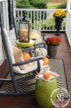 Black rocking chairs and a black-and-white chevron rug are the backbone of this outdoor room, while orange and yellow mums, accent furniture in citron green, and pumpkins brighten the space. The whole color scheme for this decor welcomes the fall season.