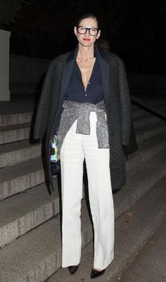 How to tuck in your shirt like Jenna Lyons: White pants, navy shirt, black textured coat, sweater tied around your waist