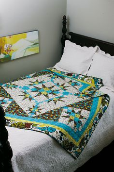 Radiance, by Judy Hansen, uses a dramatic color palette and contemporary fabrics to give this quilt pizzazz. Star quilt blocks in three sizes radiate from the quilt's center bringing focus and visual interest to this bed-size quilt.