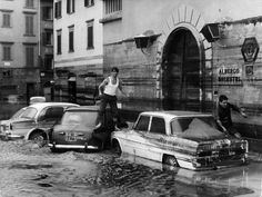 7th November 1966: Pedestrians use marooned cars as stepping stones in the flooded streets of Florence after the River Arno had burst its banks. (Keystone/Getty Images)