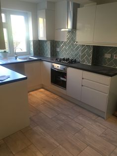On trend integrated handles - gloss white kitchen complimented with herringbone duck egg metro wall tiles with stone effect floor tiles Metro Tiles Kitchen, Corner Stove, High Gloss Kitchen, Handleless Kitchen, Modern Floor Plans, Kitchen Cabinet Layout, Quality Kitchens, Kitchen Flooring, Cool Kitchens
