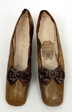 1855-65 glace kid heeled slippers with contrasting kid bow and metal buckle, owned by Empress Eugenie. Bowes Museum.