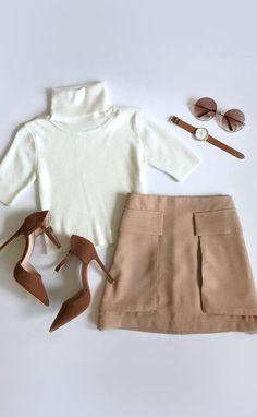 White mockneck/turtle neck w/ beige skirt (pockets?), brown/beige heels w/ ankle strap, brown sunnies, and brown watch.