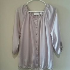 Chicos button up Blouse Thise is a Chicos Blouse, size 1, and is Taupe colored. The shirt looks more silver in the photos but is in fact a taupe color. The zoomed in photo of the tag show a more accurate representation of the color.  It 100% polyester. No trade Chico's Tops Blouses