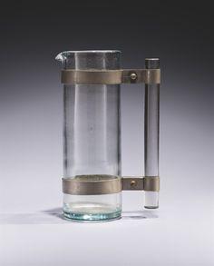 André Thuret (1898-1965) Verseuse, vers 1932 En verre incolore, la poignée tubulaire rattachée au corps par deux bagues en nickel Hauteur : 24,5 cm. (9 5/8 in.) Signée 'André Thuret' au revers de la base