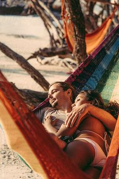 Young mixed couple relaxing in hammock on sandy beach looking at the sea by Soren Egeberg