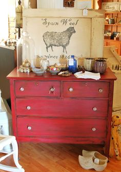 A red distressed dresser.  Stolen Kiss by Sherwin Williams, distressed and waxed. MissMustardSeed.com