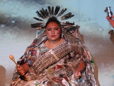 Victorious.  The seated woman in a dress made of newspapers and honey exemplifies the power of Queen Victoria and the role of the printed word as a vehicle for domination and control. By Rebecca Belmore, an Anishinaabe multimedia artist