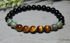Mens Grounding and Centering Gemstone Bracelet made with 8mm Tiger Eye, Black Onyx and Imperial Turquoise. Tiger Eye Properties: Helps to keep you focused, centered and grounded. It is also beneficial