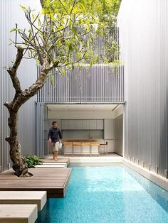 "This terrace house in Singapore was recently renovated to allow for light and natural ventilation.  A large ""void"" was placed in the middle of the house (complete with tree!) to divide the home into two sections, connected with a series of platforms over a pool.  Can you imagine?    ""Honey, dinner!""    ""Okay!  Just let me walk across our interior pool with its crystal clear water and past the huge tree in our living room."""