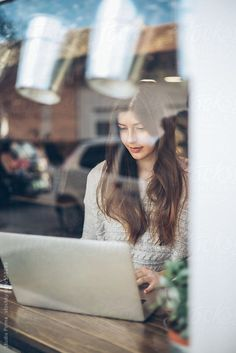 Woman sitting in coffee shop and looking at laptop.