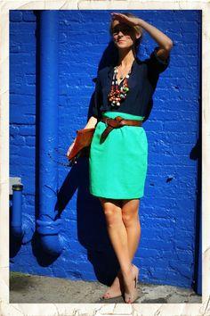 La falda es verde con un cinturón marrón.