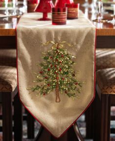 Shimmering gold weave table runner features intricate satin ribbon work Christmas tree in hues of green.