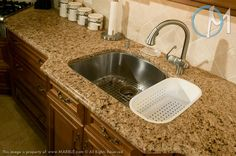 The decorative ogee edge creates a traditional atmosphere along with the elegant sink bump-out. The stainless steel sink is appropriate to cool down the warm tones in this set up.