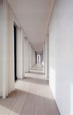 Corridor of the Ian Schrager Penthouse by John Pawson. Beautiful long corridor flanked on one side by windows.