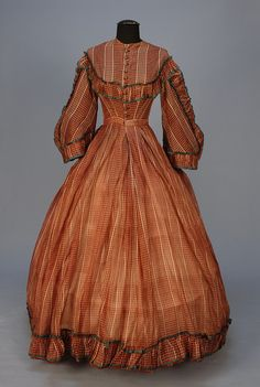 CIVIL WAR ERA TRANSPARENT WOOL PLAID DAY DRESS. 1-piece chestnut and white having bell sleeve with ruffle trim and green binding, bodice and hem with ruffle, front closure with ten Dorset type buttons, bodice lined in silk,