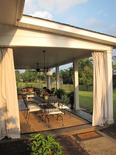 patio makeover: stained concrete slab with diamond tile pattern, lanterns hanging on posts, curtains