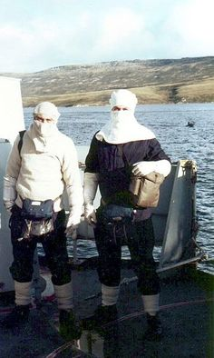 HMS Cardiff sailors dressed for action: Anti flash hood and gloves, life jacket and 'once-only'suit around waist, thick wooly items of clothing and carrying gas respirators. San Carlos waters, Falkland Islands. Date: June 1982