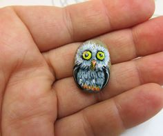 ♥♥♥ Teeny Tiny Owl Pet Rock handpainted by me on mini pebble with acrylic paints. Sealed with non-toxic glossy varnish. This little one is designed to live indoors and to keep it clean just use a soft cloth. The stone measures 7/8 high and 5/8 wide (2.1cm high x 1.6cm wide). IT IS SMAAAAALLLL :) ♥♥♥ Comes in his own mini tin for safe travels wrapped up in cotton wool so he doesnt get scratched on the journey. He really is an adorable little guy looking for a loving new home. Thanks ...