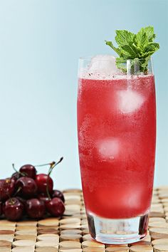"Bing cherry mojito: 1/2 large lime – cut in 1/2"" pieces 8 large mint leaves 2 teaspoons organic sugar 12 Bing cherries – pitted 3 oz (89ml) white rum 3/4 oz (22ml) Cherry liqueur (Cherry Heering) 1/2 teaspoon cherry bitters club soda or sparkling water"