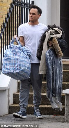 Gareth Gates moving Solemn: The 28-year-old cut a glum figure as he packed his items into a large plastic washing bag