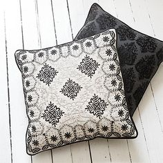 the noir black and white square pillow reflects exquisite embroidery in intricate patterns of black and white on the front, with the smooth luster of