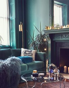 Tone-on-Tone Color--moody teal living room with lots of texture, velvet sofa and Mongolian lamb throw against glass and chrome coffee table, woodwork in various shades of dusty turquoise to teal with pops of bright blue and gold.