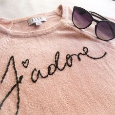 J'Adore Stitched Sweater The perfect spring sweater with Parisian vibes! Bust: 33 inches (but has some stretch). Shoulder to hem: 25 inches. 60% cotton 40% acrylic. Color is a baby pink. Elle Sweaters