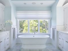 Tranquil bathroom features upper walls painted sky blue and lower walls clad in white tiled wainscoting alongside a roll top tub paired with a floor mounted vintage style tub filler placed under window dressed in white roman shade.