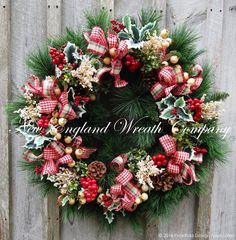 Cohasset Holiday Wreath. An abundance of long needle silk pine boughs create a lush background for a stunning gathering of holly berries and leaves mingling with pine cones, boxwood, meadow grass and